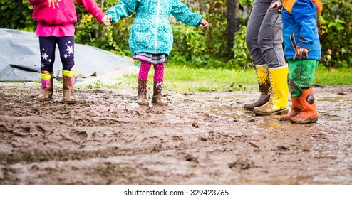 Mother playing with children. Jumping in dirty puddle with yellow, orange and pink rubber boots.