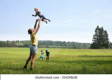 Mother playing with children, throwing a toddler in air, laughing and playing, and her older son and daughter jumping and running on a meadow. Active lifestyle, family time, modern parenting concept.