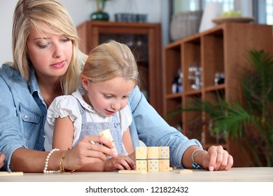 Mother playing with daughter at home