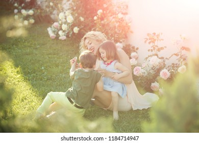 Mother playing with daughter and son in summer garden. Woman sitting with children on green grass. Happy family and childhood.