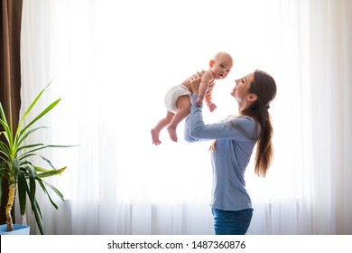 Mother playing with her baby in the bedroom. Happy loving family.