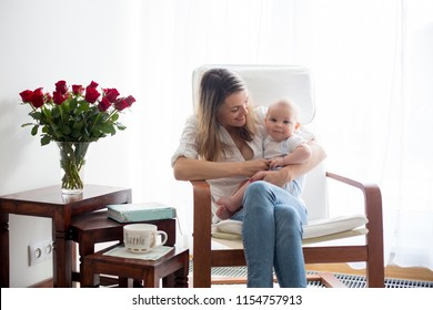 Mother, playing with her baby boy in rocking chair, reading a book to him