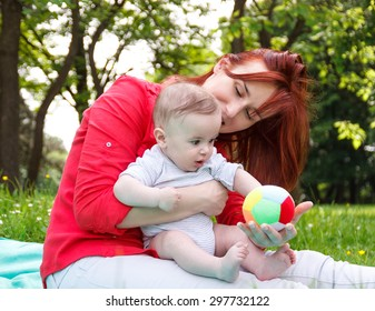 mother playing with her baby boy in park