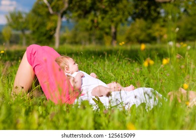Mother playing with her baby on a great sunny day in a meadow with lots of green grass and wild flowers