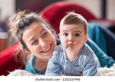 Mother is playing with her cheerful baby on the couch at home. They are looking at camera