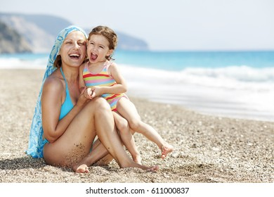 Mother playing with her daughter on the beach.