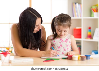 Mother playing with her little daughter, drawing together