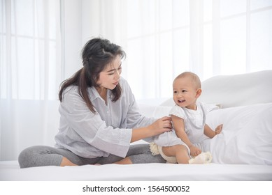 Mother playing with her little infant girl in bedroom. Parent having a happy time together. Happy infant girl smiling to mother.