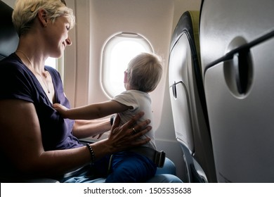 Mother playing with her one year old baby during the flight