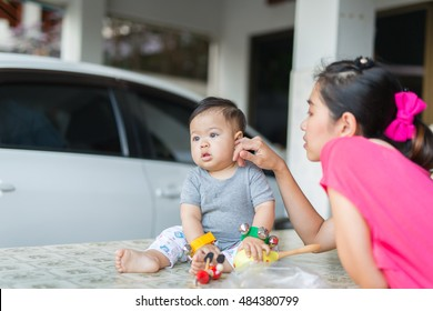 mother is playing with her son. they are always happy when they stay together. mother is the first teacher of child. in this picture, mother is teaching her son to play toy