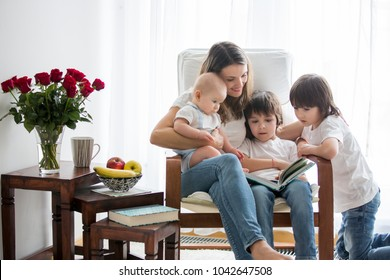 Mother, playing with her toddler boy and his older brother, reading book, smiling, breastfeeding