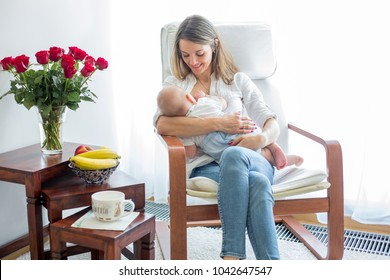 Mother, playing with her toddler boy at home in rocking chair, smiling, breastfeeding