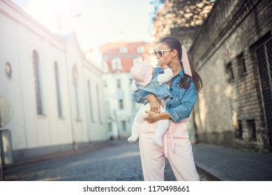 Mother playing with newborn baby, baby talking to mother. Health care family love together