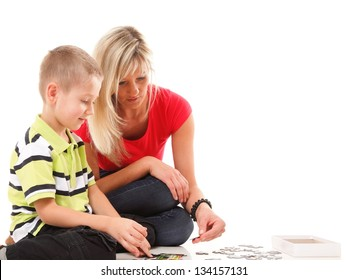 mother playing puzzle together with her son on floor isolated on white background