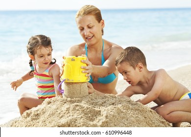Mother playing in the sand with her children.