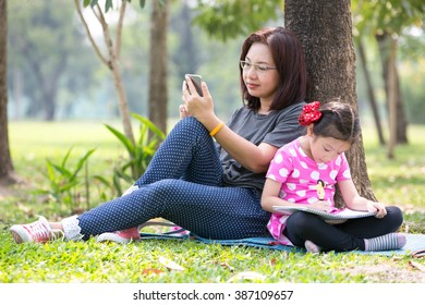 Mother playing smartphone and daughter enjoy writing in the garden