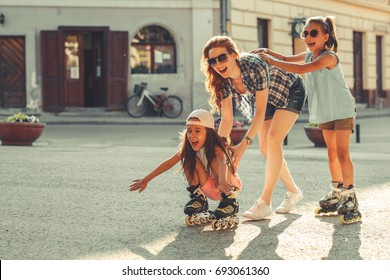 Mother plays with her daughters on street in neighborhood.They drive roller blades .Family concept.