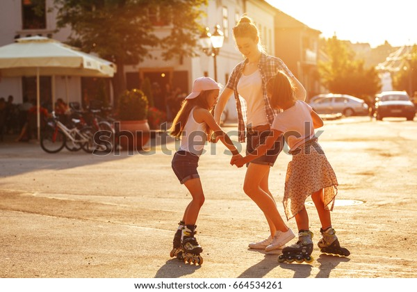 Mother plays with her daughters on street in neighborhood.They drive roller skates .Family concept.