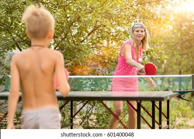 Mother plays with the son table tennis outdoors