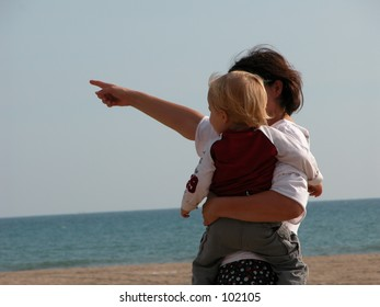 Mother pointing out something to her child on the beach