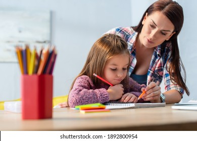 Mother pointing with pencil near positive daughter looking at notebook with blurred colored pencils on foreground