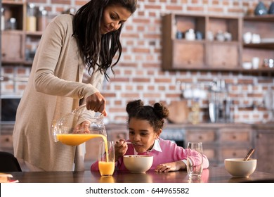mother pouring juice into daughter's glass during breakfast at home