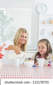Mother pouring milk into cereal bowl for daughter at breakfast time in kitchen