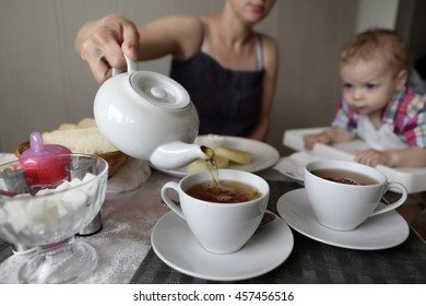 Mother pouring tea in cafe in the morning