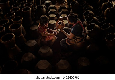 Mother pouring tea for her daughter to drink on earthenware background.