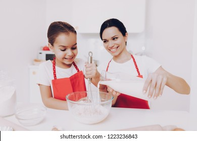 Mother and Pours Milk. mother Help Girl with Sweet Cake. White Milk for Biscuit. Mother and Daughter Preparation Milk and Flour Biscuit. Mother Help Young Girl with whis Biscuit. Cook for all Family.