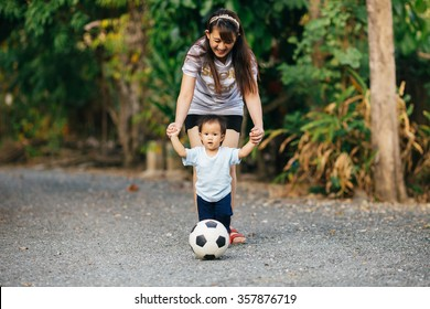 Mother practices her child to play a soccer football: film tone picture style.
