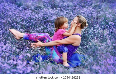 Mother practicing boat yoga pose with daughter on a violet flower background