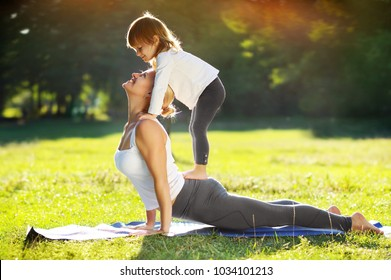 Mother practicing Upward Facing Dog yoga pose with a help of her little daughter