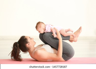 Mother practicing yoga with cute little baby at home