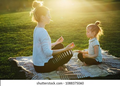 Mother practicing yoga with her daughter in the open air.