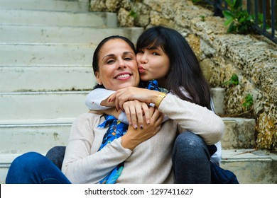 Mother with pre teenage daughter outdoor portrait.