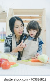 Mother preparing food and teaching her daughter cooking food in the kitchen at home, healthy food, happy family concept