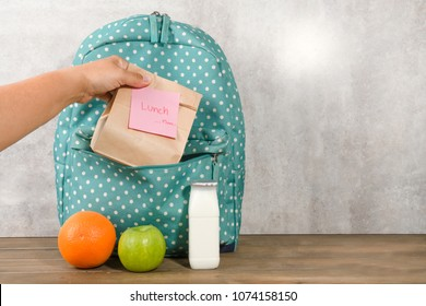 Mother preparing for her children lunch box with sandwich in paperbag orange apple and milk on wooden background. Back to school with lunch box concept.