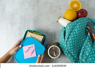 Mother preparing for her children lunch box with sandwich  orange apple and milk on gray background. Back to school with lunch box concept.