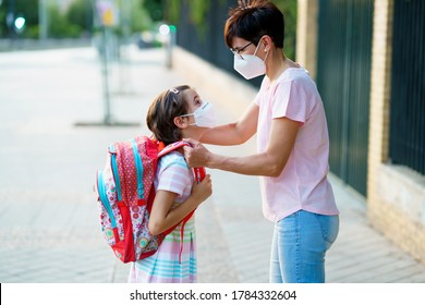 Mother preparing her little girl for the return to school wearing a mask. Back to school concept.