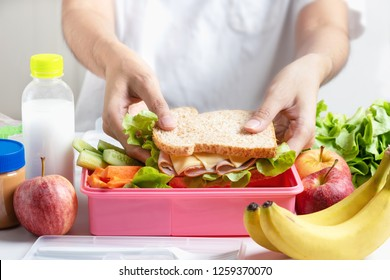 Mother preparing school lunch box set, Ham cheese sandwich with cucumber, carrot and nuts, fruits and vegetable in box. Healthy and Diet food.