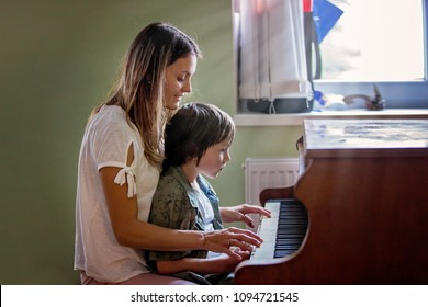 Mother and preschool child, cute boy, playing piano at home, child learning music
