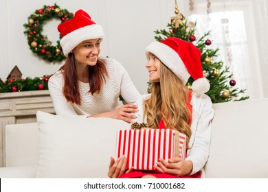 mother presenting christmas gift for excited teen daughter