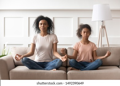 Mother and pre-teen daughter mixed-race ethnicity sit on couch in lotus position do yoga exercise practising meditation feels placidity and serenity, mental physical health lifestyle and hobby concept