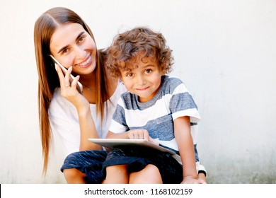 Mother and preteen son using tablet and smartphone. Modern family, back to school, trendy family look