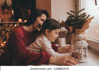 Mother and pretty daughter decorating they home with Christmas decoration. Cute little girl and her beautiful mom decorating with candles in winter weekends, posing at cozy bedroom next to the window