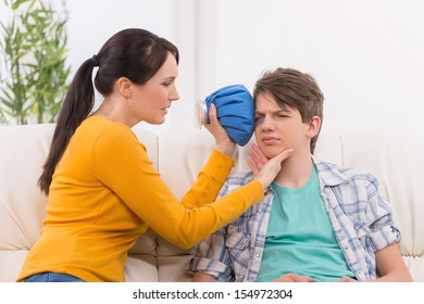 Mother and problem child. Frustrated mother putting cold bag to the injured face of her son sitting on the couch
