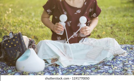 Mother pumping milk to bottles by Automatic breast pump machine in park with foliage sunset bokeh background. breastmilk is the best healthy nutrition food for newborn baby.