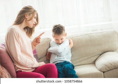 Mother punishing her little son at home. Mom scolds her child
