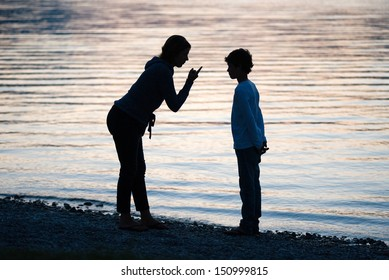 A mother is punishing her son in the evening on the beach of a lake